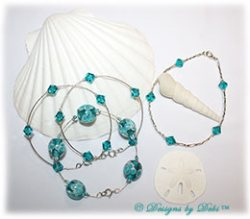 Designs by Debi Handmade Jewelry Aloha Collection Bangles and Anklet Set. Features a trio of silver bangles with aqua aloha floral beads and swarovski crystal blue zircon bicones and a matching anklet.