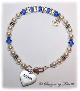 Designs by Debi Handmade Jewelry Kiara Style Pet Keepsake Bracelet in the Pearls bead combination with Sapphire (September) crystals, a heart padlock lobster clasp, Mom heart charm and additional Paw charm added at the end of the name.