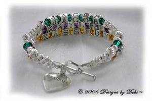 Designs by Debi Handmade Jewelry 3 strand Karen Style Bracelet in the Twist bead combination with Emerald (May), Amethyst (February) and Topaz (November) crystals, a heart toggle clasp and Grandma heart charm.
