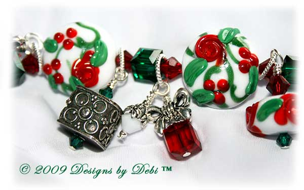 The Perfect Christmas Present Handmade Bracelet made with artisan handmade lampwork beads, Bali silver, Swarovski crystal, and cat's eye with a Bali toggle style clasp. Close-up.