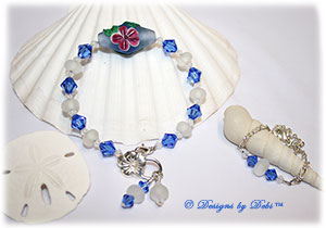 Designs by Debi Handmade Jewelry Aloha Collection Sterling Silver and Handmade Lampwork Bangle Bracelet and Anklet Set. Features a handmade etched blue bicone with pink hibiscus, etched white lampwork beads, sapphire blue swarovski bicone crystals, dangles, a flower clasp and matching anklet