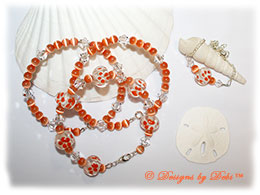 Designs by Debi Handmade Jewelry Aloha Collection Ornge Bangle Trio and Anklet Set. Features orange aloha floral glass rondelles, orange round cat's eye beads, swarovski clear crystal bicones and matching anklet.