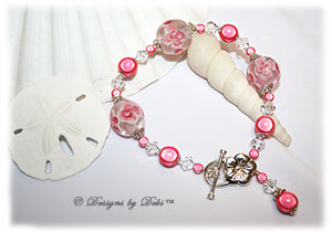 Designs by Debi Handmade Jewelry Aloha Collection Salmon Pink Bracelet featuring salmon pink aloha floral glass beads, swirled sterling silver bead caps, swarovski crystal clear bicones, salmon miracle beads, dangle and sterling flower toggle clasp.