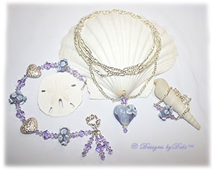 Designs by Debi Handmade Jewelry Aloha Collection Lavender Necklace, Bracelet and Anklet Set. Covertible style necklace is long figaro chain with a lavender aloha floral handmade lampwork heart pendant. Bracelet features lavender aloha floral handmade lampwork beads, bali silver embossed floral heart pillows, swarovski crystal violet and clear crystal bicones, dangles, a petite sterling floral toggle clasp and matching anklet.