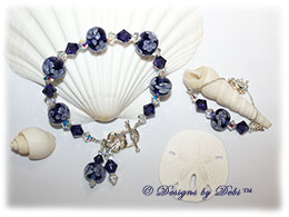 Designs by Debi Handmade Jewelry Aloha Collection Purple Bracelet and Anklet Set. Features royal purple aoha floral handmade lampwork beads, swarovski crystal purple velvet and crystal ab bicones, dangles, a silver flower toggle clasp and matching anklet.