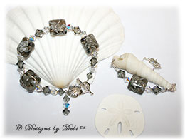 Designs by Debi Handmade Jewelry Aloha Collection Gray Bracelet and Anklet Set. Features gray squareahndmade lampwork beads with floral pattern and cz's, swarovski crystal black diamond and crystal ab bicones, dangle, sterling flower toggle clasp and matching anklet.