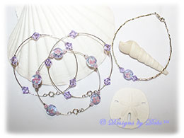 Designs by Debi Handmade Jewelry Aloha Collection Bangle Trio and Anklet Set. Features a trio of silver bangles with tanzanite and pink aloha floral beads and swarovski crystal violet bicones and a matching anklet.