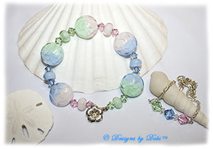 Designs by Debi Handmade Jewelry Aloha Collection Bangle Bracelet and Anklet Set. Features a set of handmade lampwork floral spree beads with a pstel gradient pattern in pink, light blue and mint green, accent beads and swarovski crystal bicones in rosaline, light sapphire and chrysolite with a sterling silver flower clasp and anklet with matching crystals.