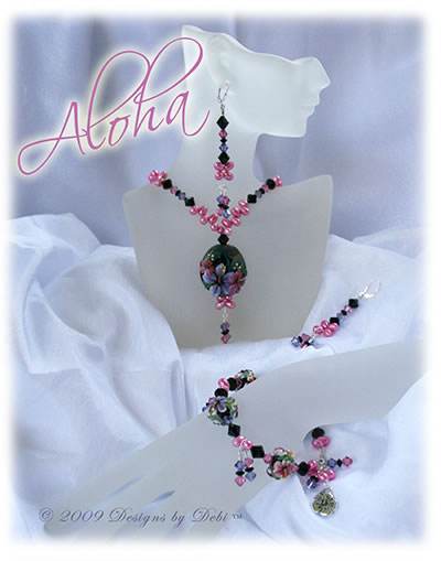Designs by Debi OOAK one of a kind set of handmade jewelry named Aloha with pink and purple hibiscus, Swarovski crystals in black, jet, pink and tanzanite, pink freshwater pearls, necklace, earrings and bracelet