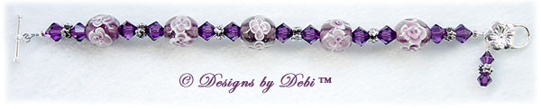 Designs by Debi Handmade Jewelry Aloha Collection Amethyst Bracelet featuring amethyst purple aloha floral glass beads, swarovski crystal amethyst bicones, silver flower spacers, a dangle and a sterling flower toggle clasp.