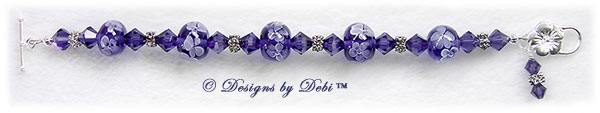 Designs by Debi Handmade Jewelry Aloha Collection Purple Bracelet featuring royal purple aloha floral handmade lampwork beads, swarovski crystal purple velvet bicones, silver flower spacers, a dangle and a sterling flower toggle clasp.