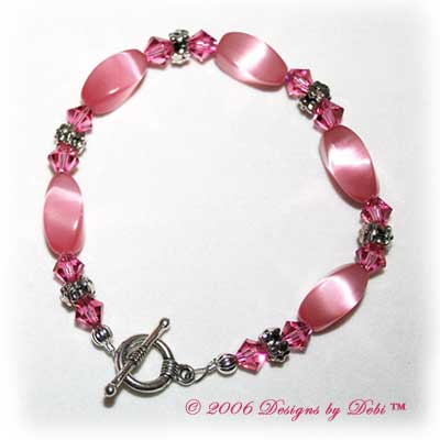 Designs by Debi Handmade Jewelry Pink Cat's Eye Twist Beads, Swarovski Crystal Rose Bicones and Silver Floral Rondelles Bracelet with a Silver Round Toggle Clasp