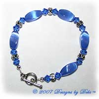 Designs by Debi Handmade Jewelry Blue Cat's Eye Twist Beads, Swarovski Crystal Sapphire Bicones and Silver Floral Rondelles Bracelet with a Silver Round Toggle Clasp