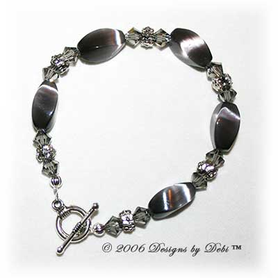 Designs by Debi Handmade Jewelry Gray Cat's Eye Twist Beads, Swarovski Crystal Black Diamond Bicones and Silver Floral Rondelles Bracelet with a Silver Round Toggle Clasp