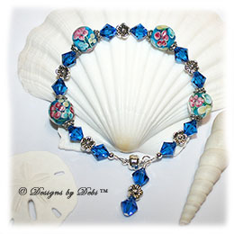 Designs by Debi Handmade Jewelry Oceans of Aloha Blue, Pink and Yellow Aloha Floral Round Beads, Silver Flowers and Swarovski Crystal Capri Blue Bicones Bracelet with a Silver Magnetic Clasp