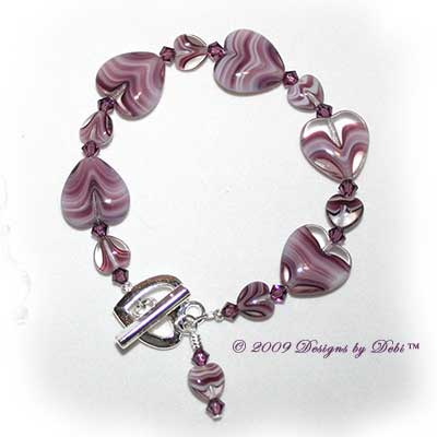 Designs by Debi Handmade Jewelry Purple Glass Hearts and Swarovski Crystal Amethyst Bicones Bracelet with a Silver Heart Toggle Clasp