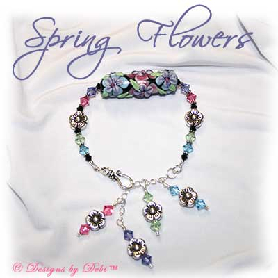 Designs by Debi Handmade Jewelry Spring Flowers Handmade Floral Lampwork Barrel Bead, Swarovski Crystal Tanzanite, Rose, Chrysolite, Aquamarine and Jet Bicones and Sterling Silver Flower Beads Bracelet with a Sterling Silver Hook Clasp and Extender Chain with Dangles ~ OOAK