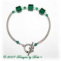 Designs by Debi Handmade Jewelry Sterling Silver Swarovski Crystal Emerald Cubes and Bicones and Crystal Spacers Curved Tube Bracelet with a Sterling Silver Claddagh Toggle Clasp