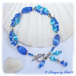 Designs by Debi Handmade Jewelry Dolphins Roaming the Ocean Sterling Silver Dolphins Bracelet with Blue and Aqua Cat's Eye Beads, Swarovski Crystal Sapphire and Aquamarine Bicones, Dangles and a Sterling Silver Twisted Rope Toggle Clasp
