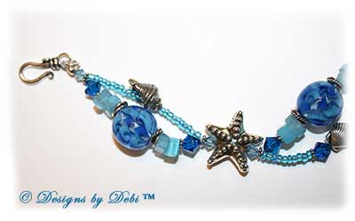 Designs by Debi Jewelry for Charity Piece for August 2010 to raise money for The Donald Paterson Recovery Fund. A one-of-a-kind artisan handmade bracelet with blue ribbon waves round handmade glass beads, thai silver starfish beads, swarovski crystal aquamarine and capri blue bicones, bali sterling silver spacer beads, sterling silver conch shells, tierracast silver scallop shells, light blue cat's eye chips, seed beads and a bali sterling silver hook and eye clasp with extender chain. OOAK one of a kind
