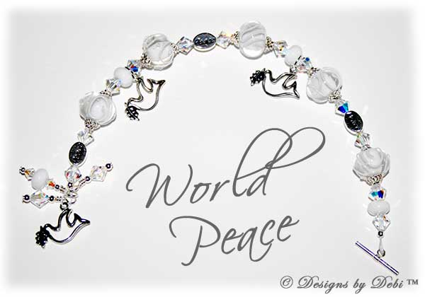 Designs by Debi Handmade Jewelry World Peace one of a kind ooak handmade white and clear lampwork and ab crystal bracelet made in honor of world peace day to raise money for Teaching Tolerance. It was made with clear lampwork beads scrolled with white, swarovski ab crystal bicones, sterling silver dove charms, sterling silver peace message beads and a sterling silver dove toggle clasp.