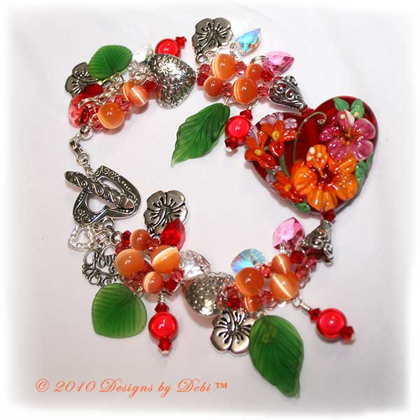 Valentine Hearts for Haiti One-of-a-Kind Handmade Bracelet made with a gorgeous artisan handmade lampwork bead, a red heart-shaped bead with pink and orange hibiscu, red, yellow and lavender flowers and green leaves; Bali fine silver heart-shaped pillow beads with embossed flowers, fancy bead caps with a swirling filigree pattern and heart toggle; Swarovski bicone and heart crystals in crystal, crystal AB, light siam, padparadscha and rose; orange cat's eye beads; sterling silver heart link chain; TierraCast hibiscus charms; red miracle beads and green glass leaves.