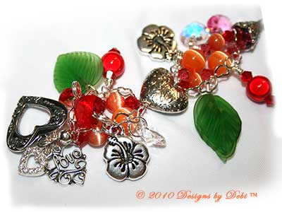 Valentine Hearts for Haiti One-of-a-Kind Handmade Bracelet made with a gorgeous artisan handmade lampwork bead, a red heart-shaped bead with pink and orange hibiscu, red, yellow and lavender flowers and green leaves; Bali fine silver heart-shaped pillow beads with embossed flowers, fancy bead caps with a swirling filigree pattern and heart toggle; Swarovski bicone and heart crystals in crystal, crystal AB, light siam, padparadscha and rose; orange cat's eye beads; sterling silver heart link chain; TierraCast hibiscus charms; red miracle beads and green glass leaves. Close-up.