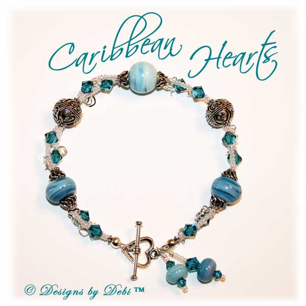 Designs by Debi Handmade Jewelry January 2011 Jewelry for Charity Piece Caribbean Hearts. Teal, white and sterling silver one of a kind lampwork bracelet to raise money for the National Cervical Cancer Coalition. The bracelet has a heart theme...handmade lamwork beads swit=rled in white and caribbean blues, swarovski teal indicolite bisone crystals, tiny pearly white seed beads, round Bali beads with a repeating heart design, sterling silver heart link chain and a sterling silver heart toggle. OOAK