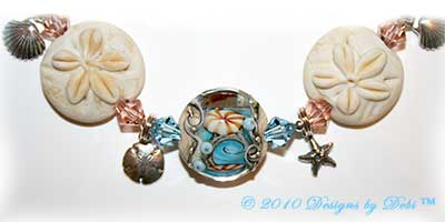 Designs by Debi Jewelry for Charity Piece for July 2010 to raise money for The Deepwater Horizon Memorial Fund. A one-of-a-kind artisan handmade bracelet with blue and beige lentil-shaped ocean within handmade glass beads, handmade glass sand dollar beads, swarovski crystal aquamarine and light peach bicones, sterling silver round beads, sterling silver sand dollar charms, sterling silver shell charms, sterling silver starfish charms, a swarovski crystal aquamarine starfish and a shiana thai sterling silver sand dollar toggle clasp. OOAK