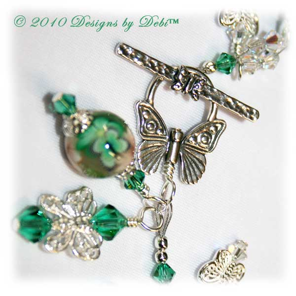 Spring Butterflies One-of-a-Kind Handmade Bracelet made with artisan handmade polymer clay round beads with green and white flowers and green butterflies, sterling silver butterflies, Swarovski crystal butterflies and Swarovski crystal AB and light emerald bicones with a sterling silver butterfly toggle style clasp. Close-up.