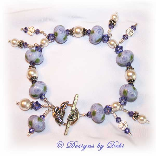 Designs by Debi Jewelry for Charity Piece for May 2010 to raise money for The Cystic Fibrosis Foundation. A one-of-a-kind artisan handmade bracelet with round handmade glass beads adorned with purple roses and green leaves, swarovski crystal tanzanite bicones, white swarovski pearls, sterling silver rose beads, sterling silver rose spacer beads and a sterling silver roses toggle clasp. OOAK