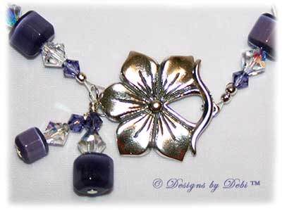 Designs by Debi Handmade Jewelry Purple Pansies one of a kind ooak handmade tanzanite purple lampwork and crystal bracelet made in honor of national alzheimer's disease awareness month to raise money for the Alzheimer's Association. It was made with purple flowers on pale lavender handmade square lampwork beads with amethyst scrolls, purple cat's eye beads, crystal ab and tanzanite crystals and sterling silver with a pansy flower toggle clasp.