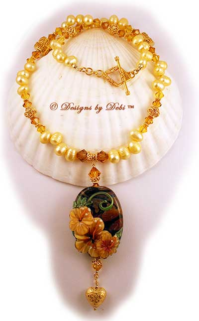 Designs by Debi September 2011 Jewelry for Charity Necklace Hawaiian Sunshine. A one of a kind necklace with a golden hibiscus handmade lampwork focal bead; golden yellow, dancing freshwater pearls, Bali vermeil squiggle pillows, filigree bicones and bead caps, daisy spacers, diamond-shaped toggle clasp and puffy heart dangle, and Swarovski crystal bicones in topaz and light topaz. One-of-a-kind OOAK