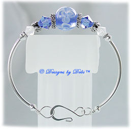 Designs by Debi Handmade Jewelry Aloha Collection Blue Fitted Bangle Bracelet featuring a royal blue aloha floral glass bead, swarovski crystal sapphire blue and white opal bicones, silver floral spacers, silver bicones, silvercurved tube beads and a hook clasp.