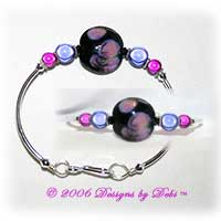 Designs by Debi Handmade Jewelry Night Water Lillies Black, Purple and Pink Artisan Handmade Lampwork Focal Bead, Swarovski Crystal Bicones and Miracle Bead Silver Fitted Bangle Bracelet with Hook Clasp
