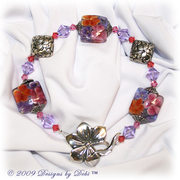 Designs by Debi Handmade Jewelry Aloha Collection Hawaiian Lei Bracelet featuring purple, pink and orange square aloha floral handmade lampwork beads, sterling lentil bead caps, bali antiqued silver embossed floral diamond-shaped pillows, swarovski crystal violet, rose and padparadscha bicones and a sterling silver large flower toggle clasp.