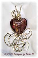 Handmade wire wrapped pendant with an amethyst foil glass heart.