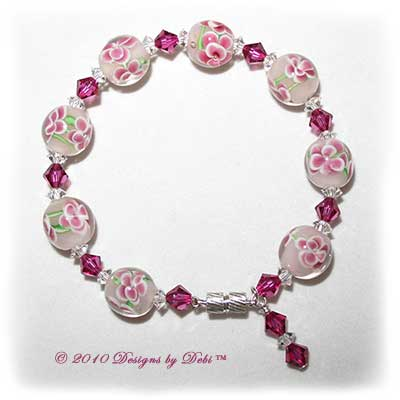 Designs by Debi Handmade Jewelry Aloha Collection Pink Bangle Bracelet featuring raspberry aloha floral glass beads, swarovski crystal fuchsia bicones and clear spacers, a dangle and a magnetic clasp.