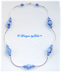 Designs by Debi Handmade Jewelry Aloha Collection Royal Blue Necklace that features blue aloha floral round beads, swarovski crystal sapphire blue bicones, silver curved noodle beads, silver corrugated round beads  and a lobster clasp.