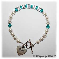 Designs by Debi Handmade Jewelry Keepsake Bracelet in the Ali Style Pearls with Antiqued Daisies bead combination with Blue Zircon (December) crystals, a heart toggle clasp and Mom heart charm. Mother's Bracelet