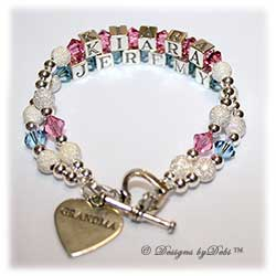 Designs by Debi Handmade Jewelry 2 strand Keepsake Bracelet in the Karen Style Stardust and Seamless Round bead combination with Rose (October) and Aquamarine (March) crystals, a heart toggle clasp and Grandma heart charm.  Grandmother's or Nana's Bracelet