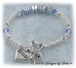 Designs by Debi Handmade Jewelry Personalized Pet Name Keepsake Bracelet in the Karen Style Twist and Stardust bead combination with Sapphire (September) crystals, a heart toggle, Mom heart charm and additional Paw heart charm.Mother's Bracelet Doggie Mom Bracelet