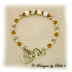 Designs by Debi Handmade Jewelry Personalized Keepsake Bracelet Wife's Bracelet, Keepsake Bracelet in the Melania Style Twist and Stardust bead combination with Topaz (November) crystals, a heart toggle and Love heart charm. Wife's Bracelet