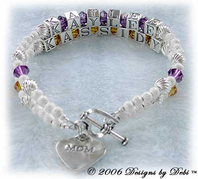 Designs by Debi Handmade Jewelry 2 strand Keepsake Bracelet in the Karen Style Twist and Stardust bead combination with Amethyst (February) and Topaz (November) crystals, a heart toggle clasp and Mom heart charm. Mother's Bracelet