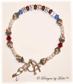 Designs by Debi Handmade Jewelry Memorial Keepsake Bracelet in the Marisol Style Twist and Stardust bead combination with Sapphire (September), Amethyst and Siam crystals, an Awareness Ribbon Heart toggle clasp and Awareness Ribbon charm.