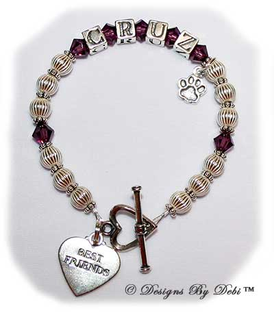 Designs by Debi Handmade Jewelry Ali Style Pet Keepsake Bracelet in the Corrugated with Antiqued Daisies bead combination, Amethyst (February) crystals, a heart toggle clasp, Best Friends heart charm and additonal Paw charm added at the end of the name.
