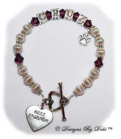 Designs by Debi Handmade Jewelry Pet Name Keepsake Bracelet in the Ali Style Corrugated with Antiqued Daisies bead combination, Amethyst (February) crystals, a heart toggle, Best Friends heart charm and additional Paw charm added at the end of the name. Dog Best Friend Bracelet