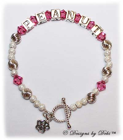 Designs by Debi Handmade Jewelry Karen Style Pet Keepsake Bracelet in the Twist and Stardust bead combination with Pink (October) crystals, a bright rope toggle clasp and Paw charm.