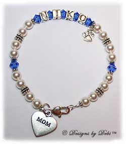 Designs by Debi Handmade Jewelry Pet Name Keepsake Bracelet in the the Kiara Style Pearls bead combination with Sapphire (September) crystals, a heart padlock lobster clasp, Mom heart charm and additional Paw charm at the end of the name. Mother's Bracelet Doggie Mom Bracelet
