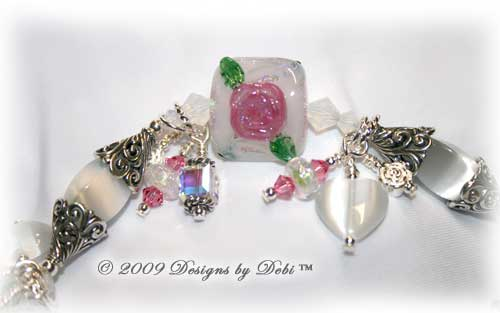 Roses on the Glistening Snow Handmade Bracelet made with artisan handmade lampwork beads, Bali silver, Swarovski crystal, and cat's eye with a toggle style clasp. Close-up.